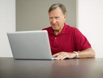 Computador portátil de utilização sênior imagens de stock royalty free