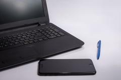 Computador, telefone esperto e pena na tabela do escritório no fundo branco Conceito do negócio Imagens de Stock Royalty Free