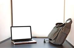 Computadora portátil abierta en el escritorio con el bolso Imagenes de archivo