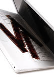 Computadora portátil blanca con las películas negativas coloreadas en un clave Imagen de archivo libre de regalías