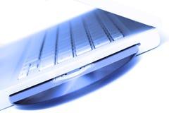 Computadora portátil blanca del tinte azul con el disco del dvd en isola de la ranura Foto de archivo