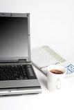 Computadora portátil, café y periódico Foto de archivo libre de regalías