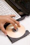 Computadora portátil con CD en la bandeja Imagen de archivo libre de regalías