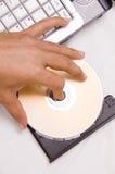 Computadora portátil con CD en la bandeja Imágenes de archivo libres de regalías