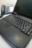 Computadora portátil con el teléfono en fondo Foto de archivo