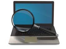 Computadora portátil con la lupa Fotografía de archivo