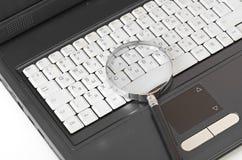 Computadora portátil con un vidrio del magnificar Imagenes de archivo