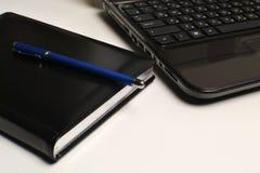 Computadora portátil, cuaderno y pluma Foto de archivo