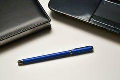 Computadora portátil, cuaderno y pluma Foto de archivo libre de regalías