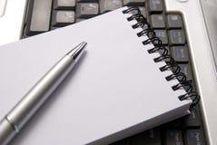 Computadora portátil, cuaderno y una pluma Fotos de archivo libres de regalías