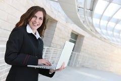 Computadora portátil de la explotación agrícola de la mujer de negocios Foto de archivo libre de regalías