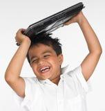 Computadora portátil de la explotación agrícola del muchacho en su cabeza Foto de archivo libre de regalías
