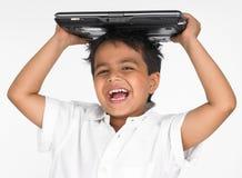 Computadora portátil de la explotación agrícola del muchacho en su cabeza Imágenes de archivo libres de regalías