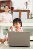 Computadora portátil de observación de la niña Imágenes de archivo libres de regalías
