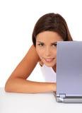 Computadora portátil de ocultación del behin de la muchacha atractiva Imagenes de archivo