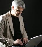 Computadora portátil de trabajo del hombre de negocios, pelo gris mayor Fotografía de archivo