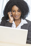 Computadora portátil del teléfono celular de la empresaria de la mujer del afroamericano Fotografía de archivo libre de regalías