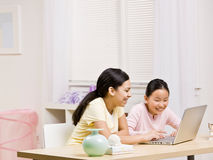 Computadora portátil del uso de las hermanas para el Internet junto Imagen de archivo