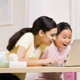 Computadora portátil del uso de las hermanas para el Internet junto Fotografía de archivo libre de regalías