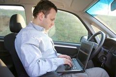 Computadora portátil detrás del volante Foto de archivo libre de regalías