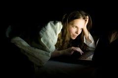 Computadora portátil en cama Fotos de archivo libres de regalías