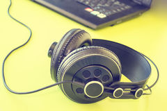 Computadora portátil en el fondo blanco y los auriculares negros Imágenes de archivo libres de regalías