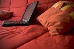 Computadora portátil en el sofá rojo con las almohadillas fotos de archivo libres de regalías