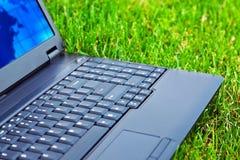 Computadora portátil en hierba Fotos de archivo libres de regalías
