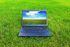 Computadora portátil en hierba Imagenes de archivo