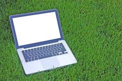 Computadora portátil en hierba Imágenes de archivo libres de regalías