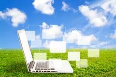 Computadora portátil en hierba y botones virtuales