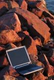 Computadora portátil entre rocas Foto de archivo libre de regalías
