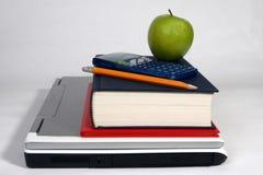Computadora portátil, libros, calculadora, lápiz y manzana Imagen de archivo libre de regalías