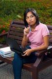 Computadora portátil linda de pensamiento del banco del estudiante universitario Imagen de archivo