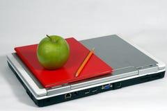 Computadora portátil, manzana verde, libro, y lápiz Imagenes de archivo