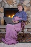 Computadora portátil mayor madura de la Navidad de la mujer de Fireplace Imágenes de archivo libres de regalías