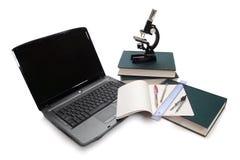 Computadora portátil, microscopio y libros. Imagenes de archivo