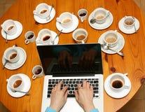 Computadora portátil (ordenador) con café, tazas (del té) Fotos de archivo