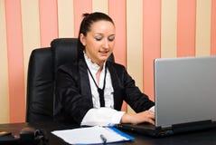 Computadora portátil que pulsa joven de la mujer de negocios Imagenes de archivo