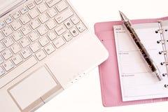 Computadora portátil, registro diario y pluma Imagenes de archivo