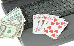 Computadora portátil, tarjetas que juegan y dólares Fotografía de archivo