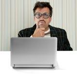 Computadora portátil tonta de la expresión de los vidrios pensativos del hombre del empollón Imagen de archivo
