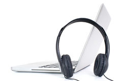 Computadora portátil y auriculares fotos de archivo