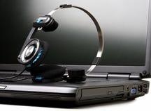 Computadora portátil y auriculares Fotografía de archivo