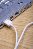 Computadora portátil y cable Imagenes de archivo