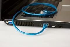 Computadora portátil y cable azul del establecimiento de una red Foto de archivo libre de regalías