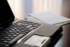 Computadora portátil y cartas en un escritorio Fotografía de archivo libre de regalías