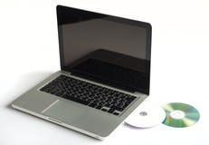 Computadora portátil y CD Imagen de archivo
