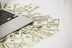 Computadora portátil y dinero Foto de archivo