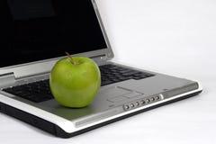 Computadora portátil y manzana Foto de archivo